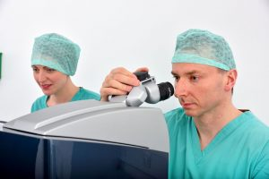 Mr Jonathan Ross with diagnostic specialist carrying out laser eye surgery